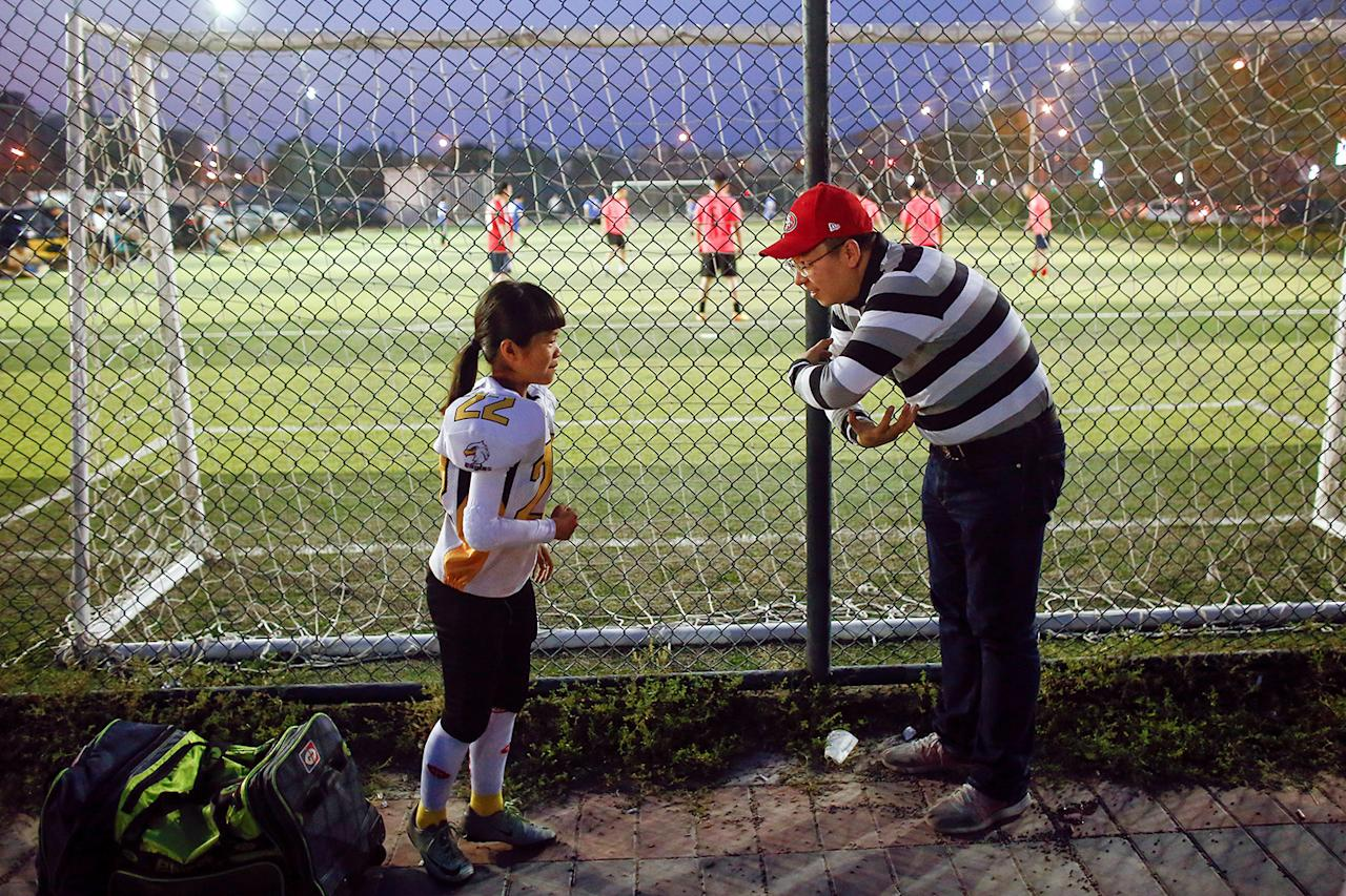 <p>Lisa Li, 9, of the Eagles listens to her father before she plays the Sharklets in their Future League American football youth league match in Beijing, May 26, 2017. (Photo: Thomas Peter/Reuters) </p>