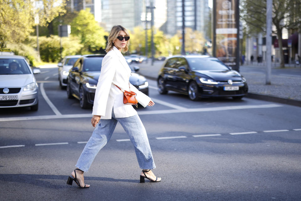 FRANKFURT AM MAIN, GERMANY - MAY 02: Influencer Victoria Tori Scheu wearing an orange micro bag by Tory Burch, light blue wide leg denim jeans pants by Levi's, a white oversized blazer by Sundarbay, a beige cropped tie top by Zara and black sandals by Essen during a street style shooting on May 02, 2021 in Frankfurt am Main, Germany. (Photo by Streetstyleshooters/Getty Images)