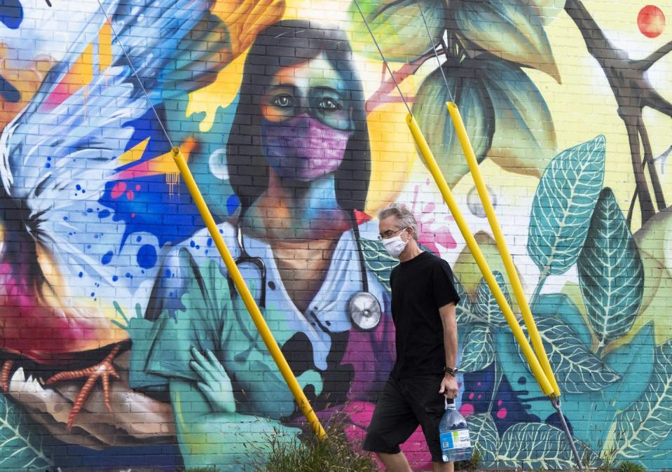A man walks by a mural of a health-care worker in scrubs