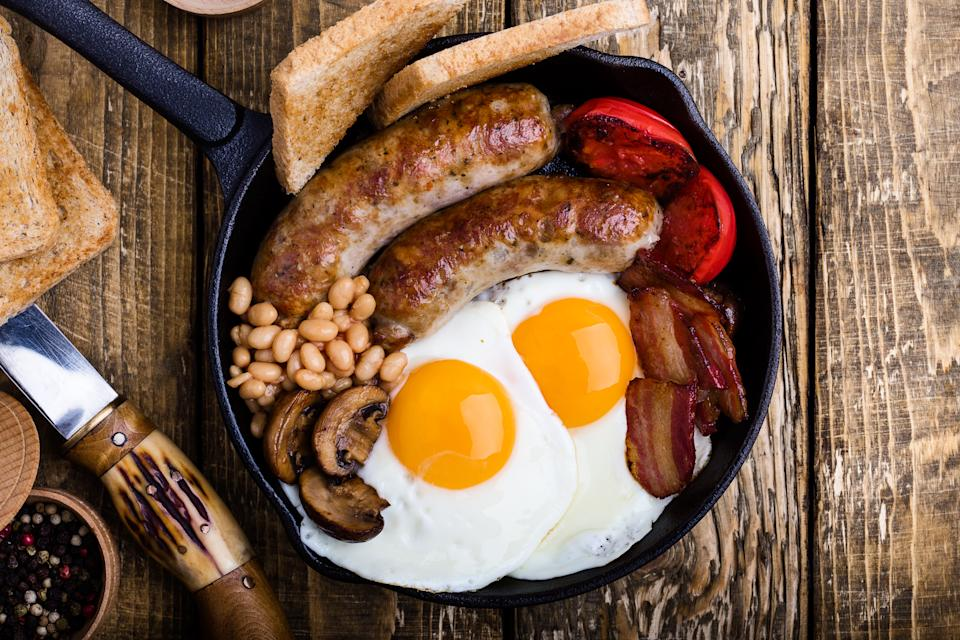 English breakfast with fried eggs, sausages, white beans, bacon, mushrooms,  toast and tomato served in cast iron skillet on rustic wooden table viewed from above, traditional British dish
