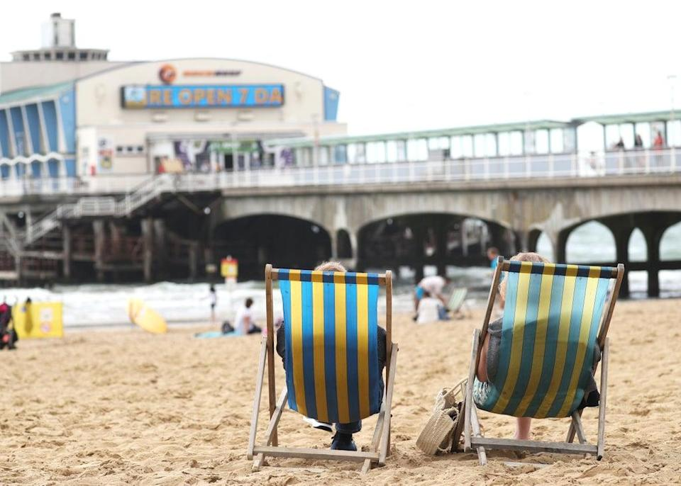 People relax on deckchairs (PA) (PA Archive)