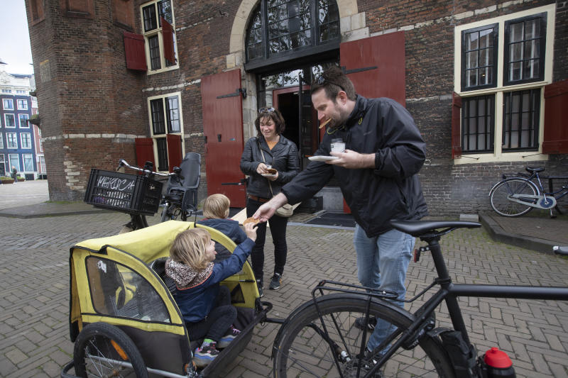 A family eats after collect their lunch at the bike trough of restaurant cafe De Waag, rear, in Amsterdam, Netherlands, Saturday, May 2, 2020. The use of bicycles is already widespread in The Netherlands, but new ways are being found for bicycle use in a partial lockdown. Countries across the world seek to get their economies back on track after coronavirus lockdowns are over, some people are encouraging the use of bicycles as a way to avoid unsafe crowding on trains and buses. (AP Photo/Peter Dejong)