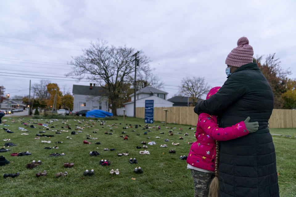Theresa McGarity, left, embraces her granddaughter, Blake, 8, while remembering her mother, Carolyn Wilson, during an art installation vigil with shoes representing residents in Macomb County who died from COVID-19 in Mount Clemens, Mich., Friday, Oct. 30, 2020. Wilson, who died in April at 76 years old, was a God-fearing woman and had been teaching Blake how to crochet. On Friday night, as McGarity brought Blake to the art installation, a raucous pro-Trump demonstration down the street could be heard as they read the age and hometown of each of their dead. (AP Photo/David Goldman)