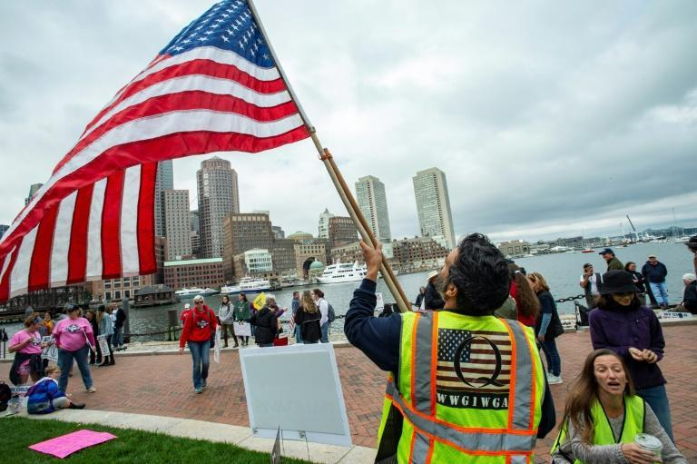 A man in a QAnon vest waves a US flag as demonstrators gather on October 5, 2020 to protest mandatory flu vaccines for children in Boston, Massachusetts
