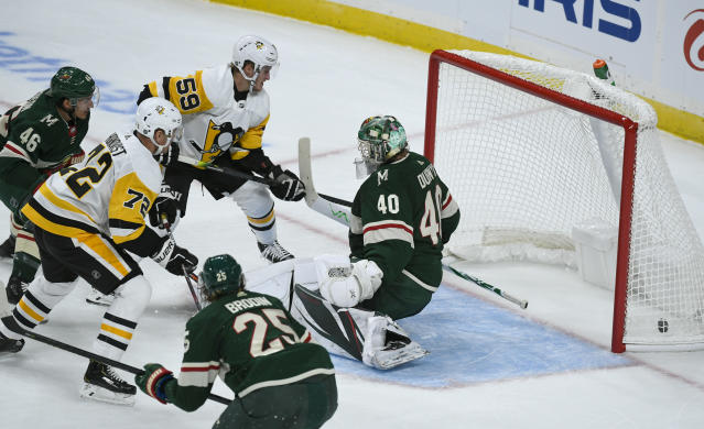 Pittsburgh Penguins winger Patric Hornqvist, left, shoots the puck past Minnesota Wild goalie Devan Dubnyk (40) to score as Penguins winger Jake Guentzel (59), Wild defenseman Jared Spurgeon (46)and Wild defenseman Jonas Brodin (25) watch during the first period of an NHL hockey game Saturday, Oct. 12, 2019, in St. Paul, Minn. (AP Photo/Craig Lassig)