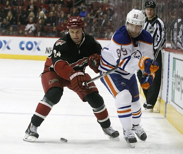 Phoenix Coyotes center Kyle Chipchura (24) and Edmonton Oilers center Sam Gagner (89) battle for the puck in the first period of an NHL hockey game, Tuesday, Dec. 31, 2013, in Glendale, Ariz. (AP Photo/Rick Scuteri)