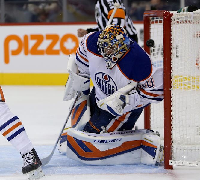 Winnipeg Jets' Michael Frolik puts the puck over the shoulder of Edmonton Oilers goaltender Richard Bachman (30) during the second period of a preseason NHL hockey game in Winnipeg, Manitoba, Tuesday, Sept. 17, 2013. (AP Photo/The Canadian Press, Trevor Hagan)