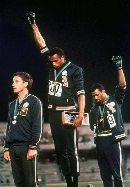 FILE - In this Oct. 16, 1968, file photo, extending gloved hands skyward in racial protest, U.S. athletes Tommie Smith, center, and John Carlos stare downward during the playing of national anthem after Smith received the gold and Carlos the bronze for the 200 meter run at the Summer Olympic Games in Mexico City. Australian silver medalist Peter Norman is at left. The U.S. Olympic and Paralympic Committee is signaling willingness to challenge longstanding IOC rules restricting protests at the Olympics, while also facing backlash from some of its own athletes for moves viewed by some as not being driven by sufficient athlete input. (AP Photo/File)