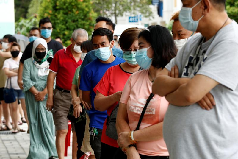 Voters wear protective face masks as they queue up at a polling station during Singapore's general election, amid the coronavirus disease (COVID-19) outbreak, in Singapore July 10, 2020. REUTERS/Edgar Su