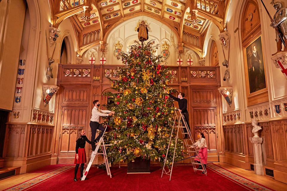 For single use only in relation to the Christmas displays at Windsor Castle in 2020, not to be archived, sold on or used out of context. Undated handout photo issued by the Royal Collection Trust of Royal Collection Trust staff put the finishing touches on the 20-foot-high Christmas tree in St George's Hall, the largest room in Windsor Castle, which can be enjoyed by visitors to the Castle from Thursday.