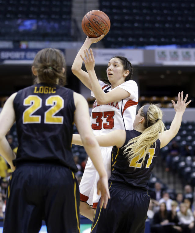Nebraska guard Rachel Theriot (33) shoots over Iowa guards Samantha Logic, left, and Sadie Murren in the second half of an NCAA college basketball game in the finals of the Big Ten women's tournament in Indianapolis, Sunday, March 9, 2014. Nebraska defeated Iowa 72-65. (AP Photo/Michael Conroy)