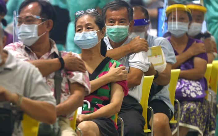 People rest after receiving a dose of the Moderna vaccine at an exhibition hall in Taipei City - Reuters