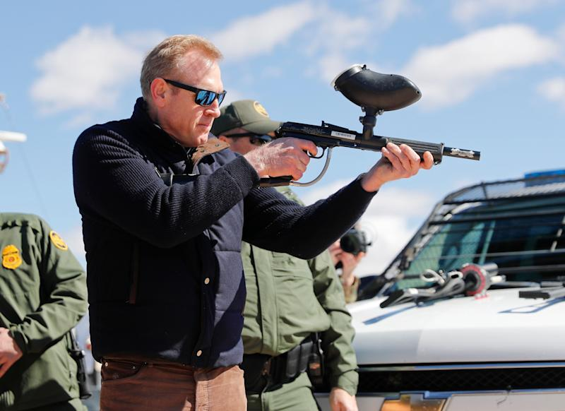 Acting Secretary of Defense Patrick Shanahan, center, fires a modified paintball gun that shoots pepper balls during a tour of the US-Mexico border at Santa Teresa Station in Sunland Park, N.M. on Feb. 23, 2019. (Photo: Pablo Martinez Monsivais/AP)