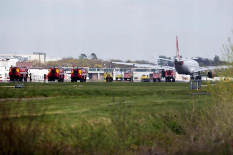 A Virgin Atlantic Airbus A330 aircraft is towed away from the runway at Gatwick Airport, England after it was forced to return and make an emergency landing Monday April 16, 2012. Virgin Atlantic said four people suffered minor injuries after a plane bound from Britain to Florida made an emergency landing at London's Gatwick Airport on Monday. The airline said that all passengers and crew have safely disembarked the plane, but declined to provide further details on the nature of the injuries, who was affected or what caused the emergency landing.(AP Photo/Steve Parsons/PA) UNITED KINGDOM OUT