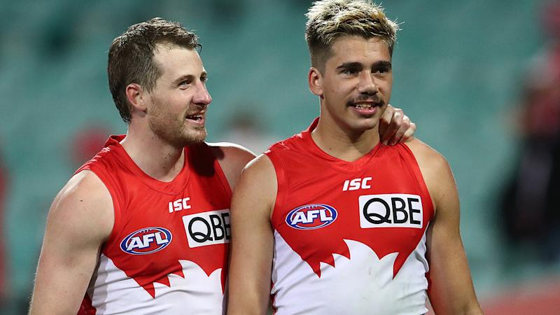 Sydney Swans players Harry Cunningham and Elijah Taylor are pictured walking off the field.