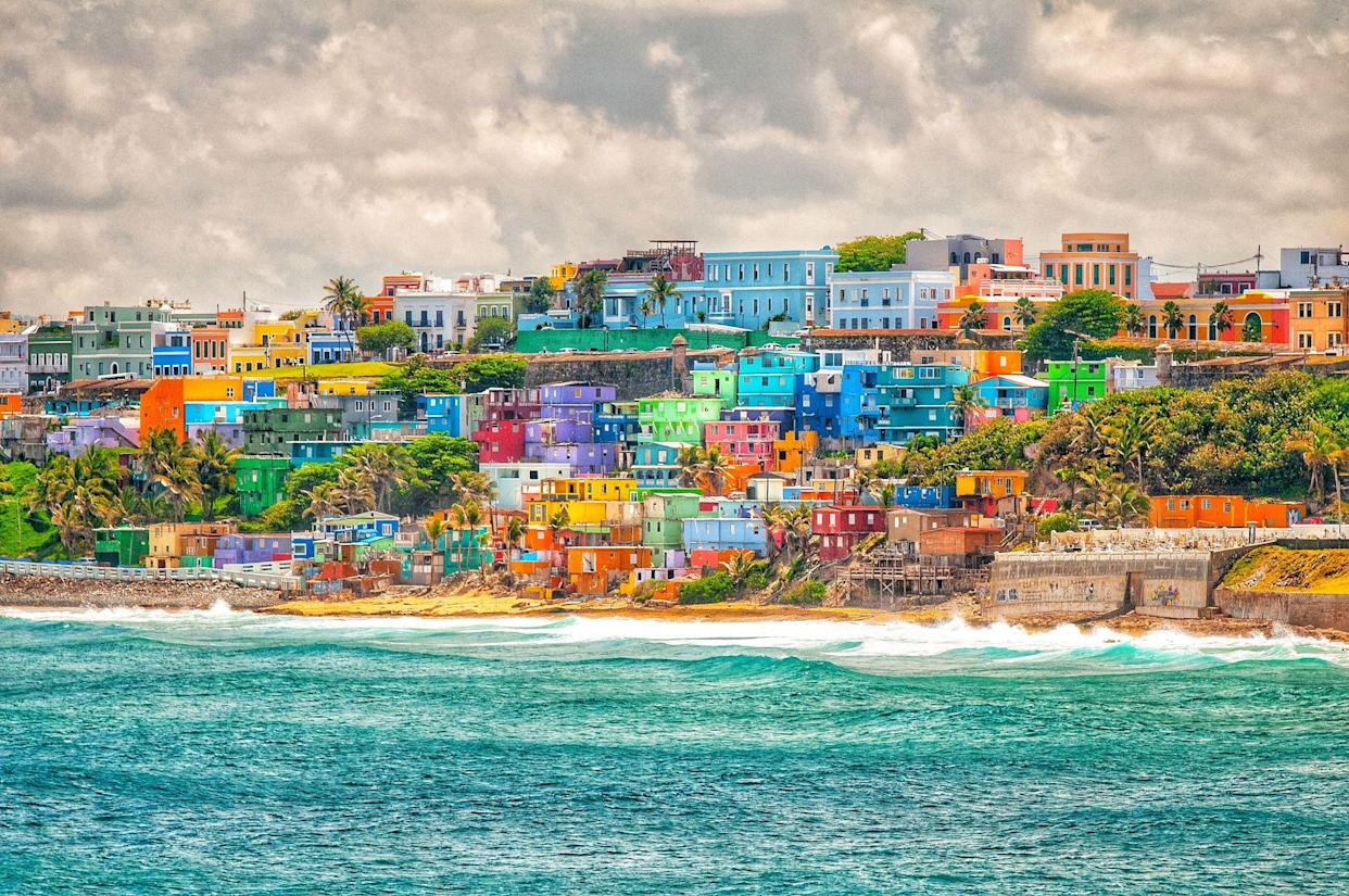 Colorful house stacked on a hill over looking ocean in Puerto Rico.