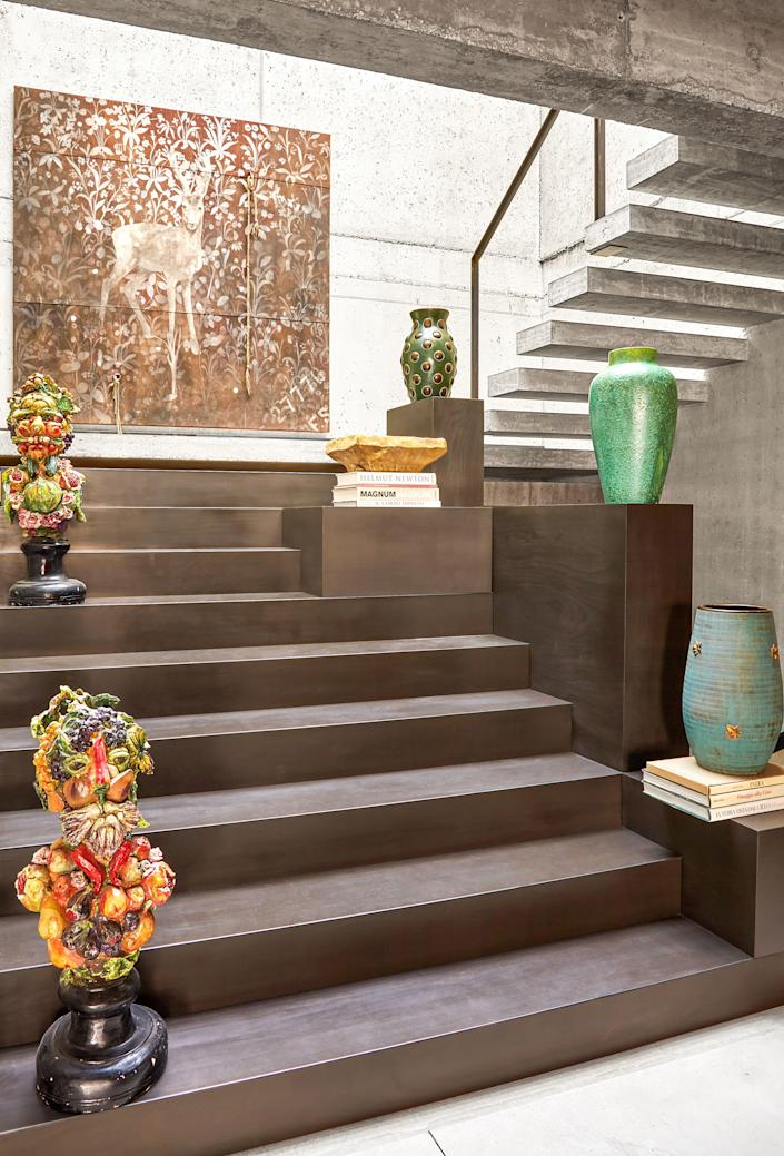 "<div class=""caption""> Vintage vases and Giuseppe Arcimboldo–inspired ceramic busts line a black iron stairway. </div> <cite class=""credit"">Oberto Gili</cite>"