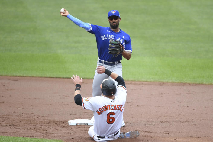 Toronto Blue Jays second baseman Marcus Semien turns a double play during the first inning as Ryan Mountcastle slides into second base baseball game on Sunday, June 20, 2021, in Baltimore. (AP Photo/Terrance Williams)