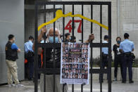 """A protester stands behind a mock prison while police officers do search to other protesters during a protest against an election committee that will vote for the city's leader in Hong Kong Sunday, Sept. 19, 2021. Hong Kong's polls for an election committee that will vote for the city's leader kicked off Sunday amid heavy police presence, with chief executive Carrie Lam saying that it is """"very meaningful"""" as it is the first election to take place following electoral reforms. (AP Photo/Vincent Yu)"""
