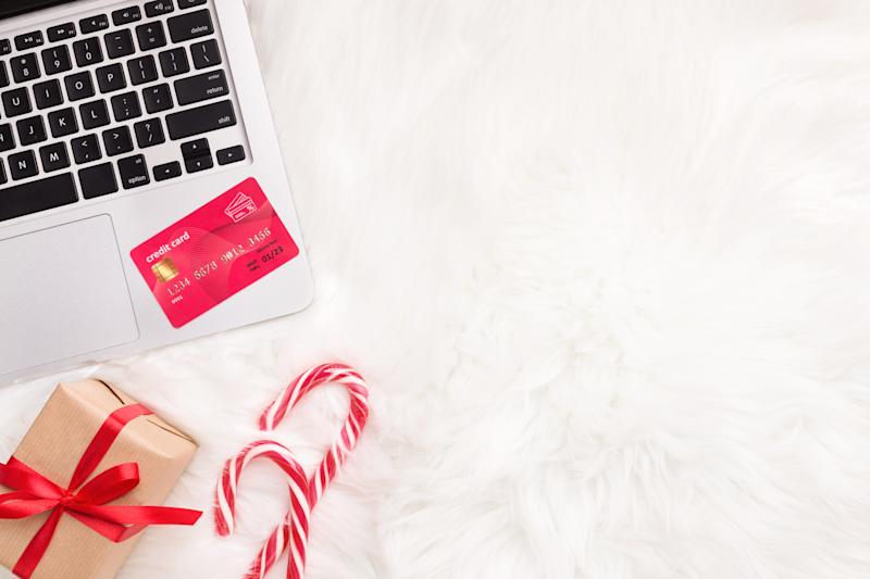Shopping online with laptop and credit card on white fur background, copy space