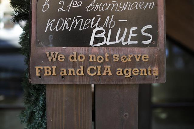 """A sign that says """"We do not serve FBI and CIA agents,"""" hangs outside a restaurant on the opening day of the 2014 Winter Olympics, Friday, Feb. 7, 2014, in Krasnaya Polyana, Russia. (AP Photo/Jae C. Hong)"""