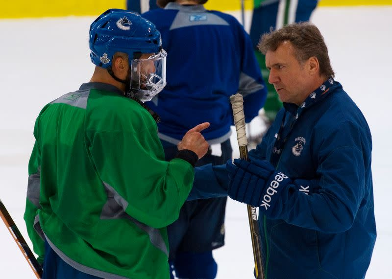 Vancouver Canucks Malhotra talks with associate coach Bowness during a team hockey practice for the NHL Stanley Cup in Vancouver