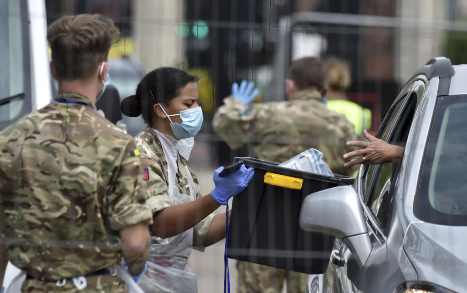 Members of the army work at a coronavirus testing station set up in Victoria Park in Leicester, England, Tuesday June 30, 2020. The British government has reimposed lockdown restrictions in the English city of Leicester after a spike in coronavirus infections, including the closure of shops that don't sell essential goods and schools. (AP Photo/Rui Vieira)