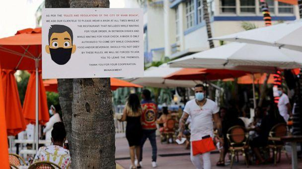 PHOTO: A sign informs customers at the Edison Hotel restaurant about wearing a protective face mask during the coronavirus pandemic, July 24, 2020, along Ocean Drive in Miami Beach, Fla. (Lynne Sladky/AP)