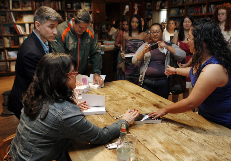 "Author E L James, left, signs copies of her new erotic fiction ""Fifty Shades of Grey"" during a book signing in Coral Gables, Fla., Sunday, April 29, 2012. (AP Photo/Jeffrey M. Boan)"
