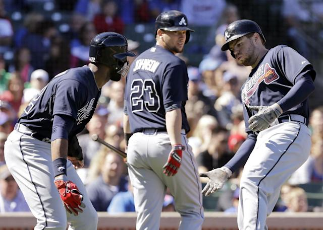 Atlanta Braves' Freddie Freeman, right, celebrates with Jason Heyward, left, after hitting a two-run home run as Chris Johnson, center, looks on during the first inning of a baseball game against the Chicago Cubs, Sunday, Sept. 22, 2013, in Chicago. (AP Photo/Nam Y. Huh)