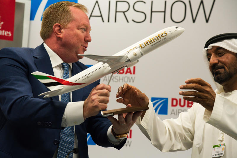 Boeing Commercial Airplanes president and CEO Stanley A. Deal, left, hands Sheikh Ahmed bin Saeed Al Maktoum, the chairman and CEO of the Dubai-based long-haul carrier Emirates, a model of a Boeing 787 Dreamliner at the Dubai Airshow in Dubai, United Arab Emirates, Wednesday, Nov. 20, 2019. Dubai's carrier Emirates announced Wednesday a firm order for 30 Boeing 787 Dreamliners in deal valued at $8.8 billion. (AP Photo/Jon Gambrell)