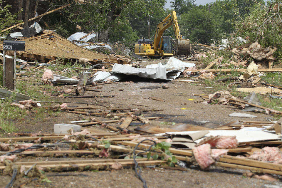 A excavator is used to clean along Lunceford Lane in Calhoun City, Mississippi, Monday, May 3, 2021, following Sunday's severe weather that destroyed several blocks of business and homes. (Thomas Wells/The Northeast Mississippi Daily Journal via AP)