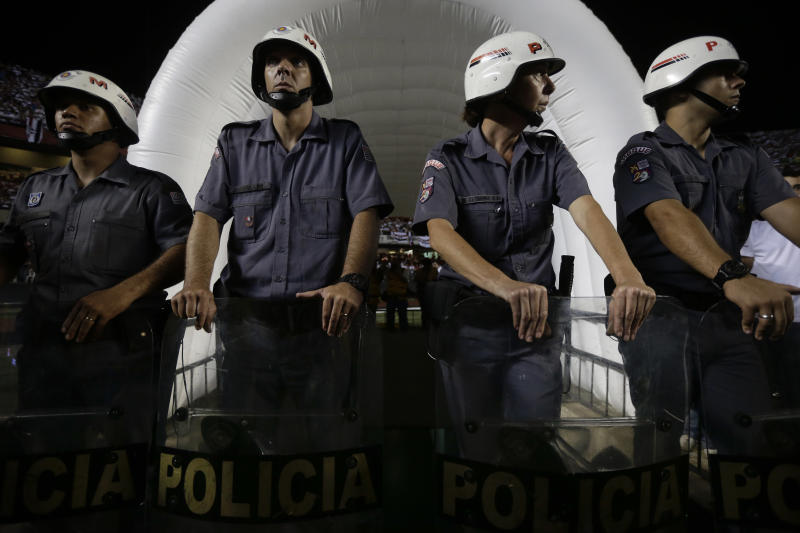 Police officers stand guard the entrance to Argentina's Tigre's dressing room after a fight among teams' members at the end of the first half of the Copa Sudamericana final soccer match against Brazil's Sao Paulo FC in Sao Paulo, Brazil, Wednesday, Dec. 12, 2012. (AP Photo/Felipe Dana)
