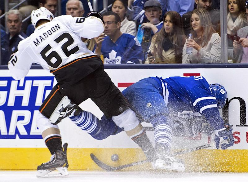 Toronto Maple Leafs forward Jay McClement, right, get hit into the boards by Anaheim Ducks forward Patrick Maroon (62) during the second period of an NHL hockey game in Toronto on Tuesday, Oct. 22, 2013. (AP Photo/The Canadian Press, Nathan Denette)