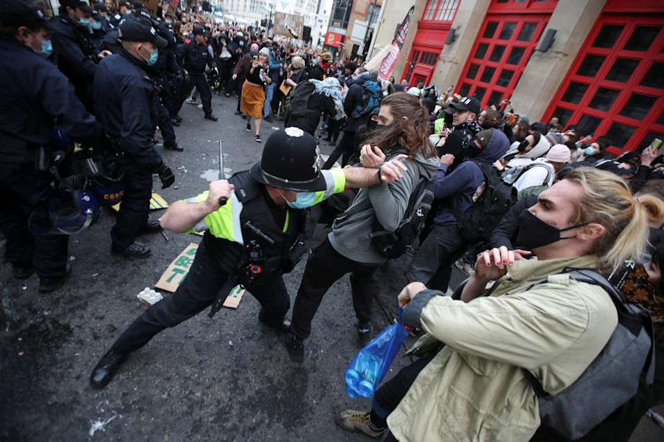 <p>A police officers attempts to control the crowd during a protest against a new proposed policing bill, in Bristol, Britain, March 21, 2021. REUTERS/Peter Cziborra</p>