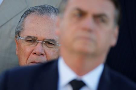 Brazil's Economy Minister Guedes looks on near Brazil's President Bolsonaro during a ceremony of hoisting the national flag in front the Planalto Palace in Brasilia
