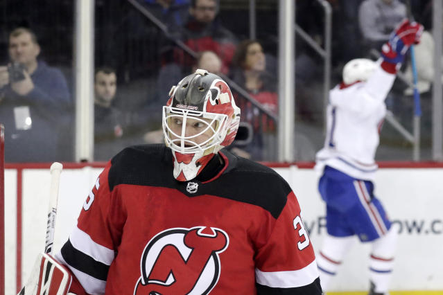 New Jersey Devils goaltender Cory Schneider, left, looks on as Montreal Canadiens left wing Paul Byron, back right, celebrates after scoring a goal on him during the third period of an NHL hockey game, Monday, Feb. 25, 2019, in Newark, N.J. The Devils won 2-1. (AP Photo/Julio Cortez)