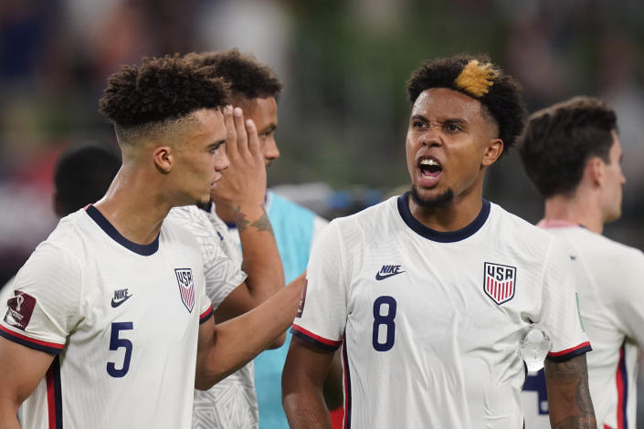 United States' Antonee Robinson (5) and Weston McKennie (8) celebrate with fans after their win over Jamaica in a FIFA World Cup qualifying soccer match, Thursday, Oct. 7, 2021, in Austin, Texas. (AP Photo/Eric Gay)