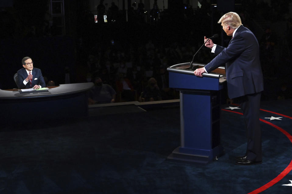 FILE - President Donald Trump gestures to moderator Chris Wallace of Fox News during the first presidential debate in Cleveland on Sept. 29, 2020. Leaders of the Commission on Presidential Debates and moderators of all three debates gathered for a remote debrief Monday night. Two takeaways: increased early voting means the commission is considering earlier debates, and the mute button may be here to stay. (Olivier Douliery/Pool vi AP, File)