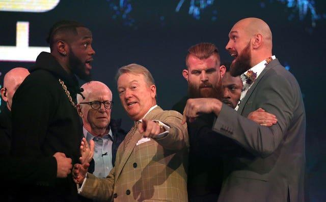 Deontay Wilder (left) and Tyson Fury (right) react as promoter Frank Warren (centre) keeps them apart during a press conference