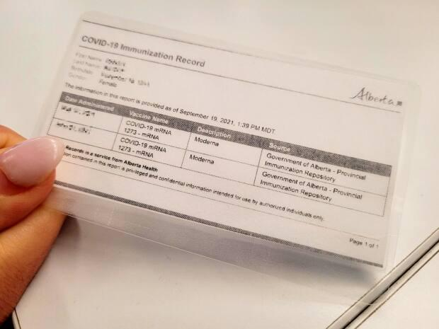 A printed copy of an individual's Alberta COVID-19 immunization record. The program allows businesses and venues to operate without capacity limits if they require proof of vaccination or a negative test result from anyone entering. (Sarah Rieger/CBC - image credit)