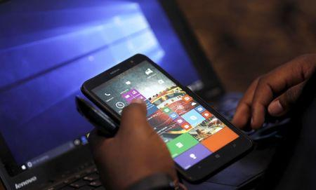 A Microsoft delegate checks applications on a smartphone during the launch of the Windows 10 operating system in Kenya's capital Nairobi