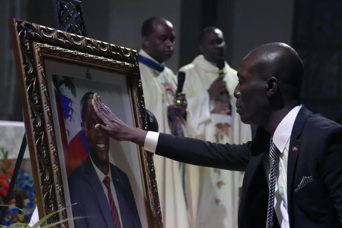 A mourner reaches out to touch a photograph of Haiti's assassinated President Jovenel Moïse, during a memorial service at Notre Dame d'Haiti Catholic Church on Thursday, July 22, 2021, in the Little Haiti neighborhood of Miami. Miami's Haitian Consul General hosted the service for members of the city's large Haitian community to pray for the troubled nation and pay their respects to the president, who was slain in a July 7 attack at his home which left his wife seriously wounded.(AP Photo/Rebecca Blackwell)