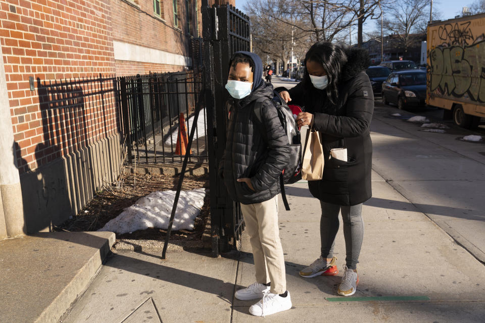 FILE - In this Feb. 25, 2021 file photo, a student waits to enter Meyer Levin Middle School as his mother puts his lunch in his backpack, in New York. With COVID-19 cases soaring nationwide, school districts across the U.S. are yet again confronting the realities of a polarized country and the lingering pandemic as they navigate mask requirements, vaccine rules and social distancing requirements for the fast-approaching new school year.(AP Photo/Mark Lennihan, File)