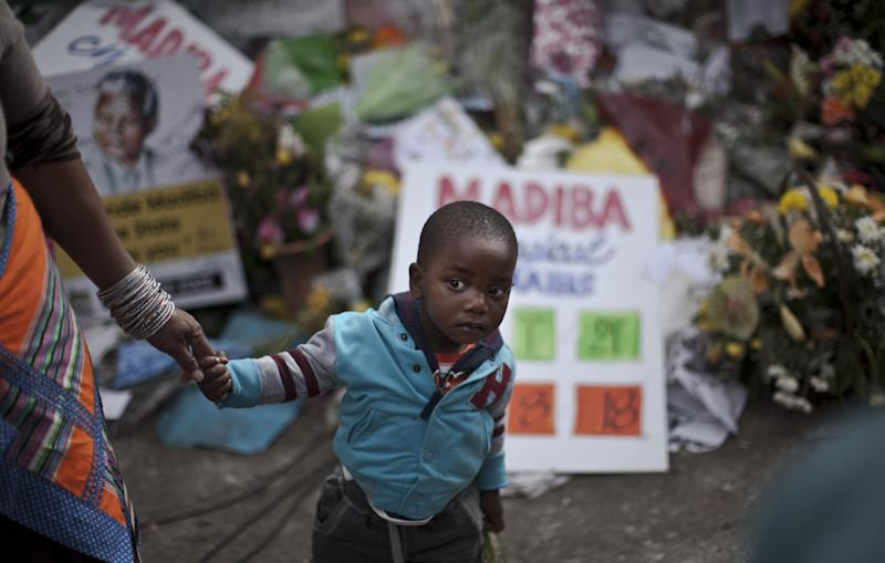 A South African child holding his grandmother's hand looks at well-wishers singing in support of former South African President Nelson Mandela outside the Mediclinic Heart Hospital where he is being treated in Pretoria, South Africa, Friday, July 5, 2013. Mandela, who was hospitalized on June 8, remains in critical but stable condition according to the office of President Jacob Zuma, who visited the anti-apartheid leader on Thursday. (AP Photo/Muhammed Muheisen)