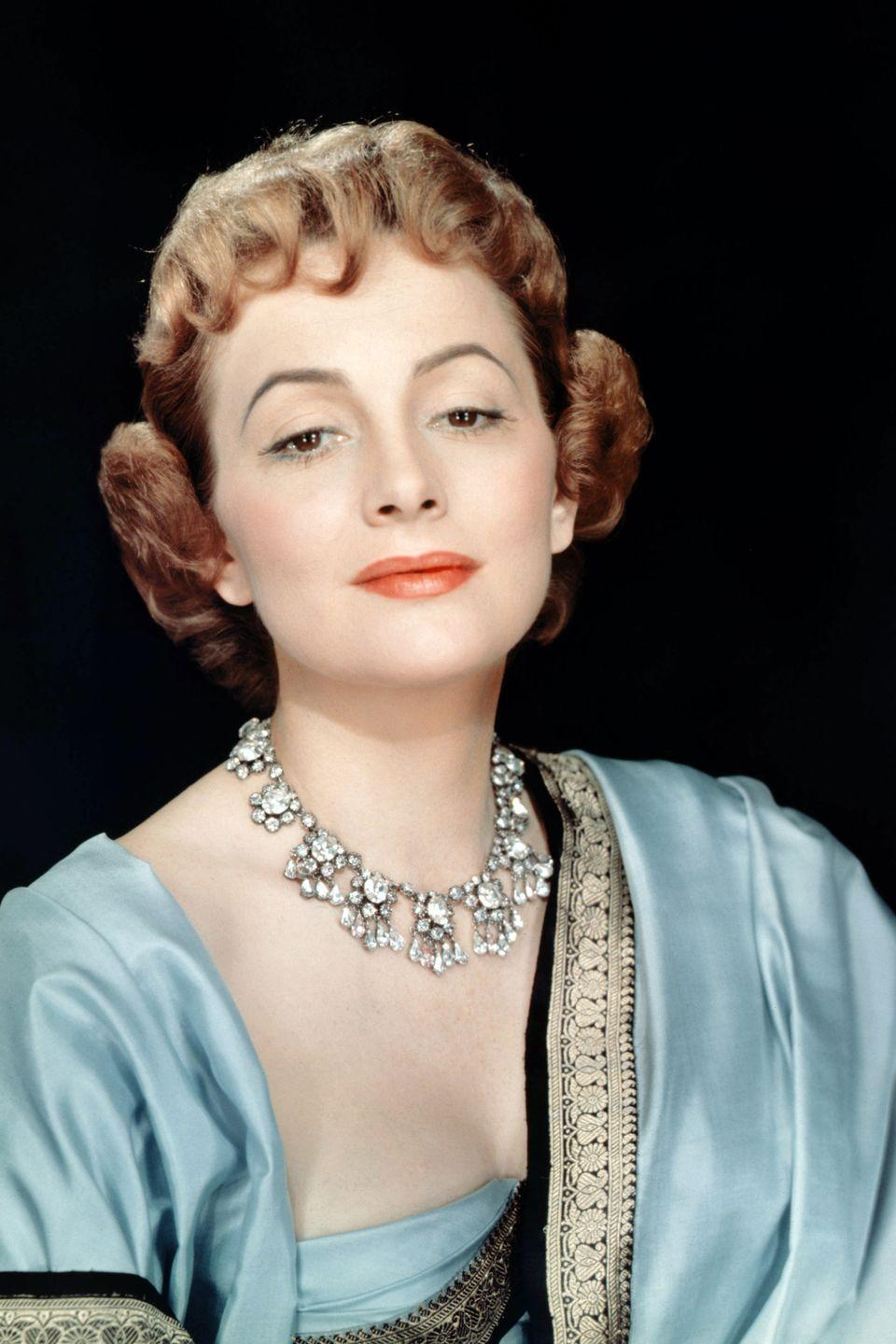 <p>Draped in a regal blue robe and diamond necklace. </p>