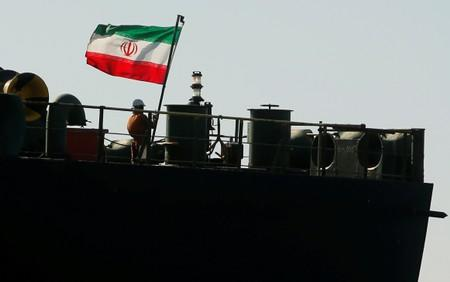 A crew member raises the Iranian flag at Iranian oil tanker Adrian Darya 1, before being named as Grace 1, as it sits anchored after the Supreme Court of the British territory lifted its detention order, in the Strait of Gibraltar