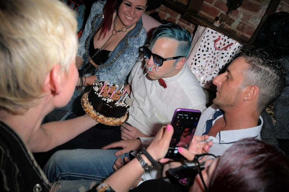 Michael Alig with blue hair and wearing sunglasses blows out the birthday candles of a cake