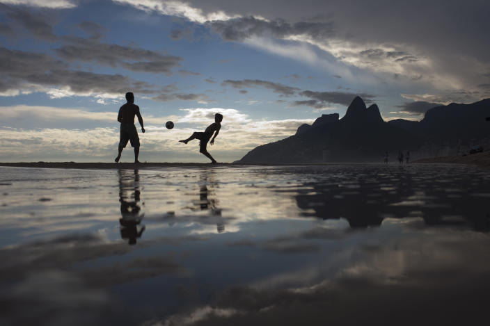 "FILE - In this Dec. 16, 2011 file photo, two men play soccer at Ipanema beach in Rio de Janeiro, Brazil. The bossa nova song, ""The Girl From Ipanema"" is turning 50, and to its legions of fans, the decades have only heightened its allure. The tune inspired by a young woman who passed the songwriters in a beach side bar on her way to the waters of Ipanema beach, carries within its chords and lyrics an image of a city that's light and easy, palm trees and blue sky, a sun-kissed life without care. (AP Photo/Felipe Dana, File)"