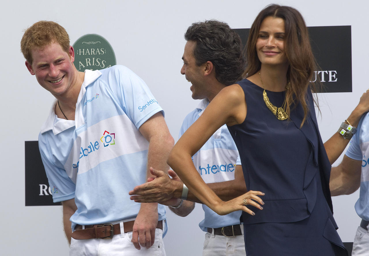 Britain's Prince Harry, left, smiles after greeting Brazil's model Fernanda Motta, right, during the award ceremony after playing a charity polo match in Campinas, Brazil, Sunday March 11, 2012. Prince Harry is in Brazil at the request of the British government on a trip to promote ties and emphasize the transition from the upcoming 2012 London Games to the 2016 Olympics in Rio de Janeiro. (AP Photo/Andre Penner)